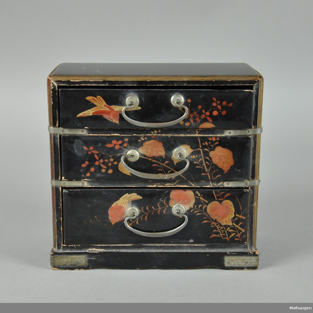 Svartlakkert lekekommode av tre med tre skuffer. Skuffene har metallhåndtak og kommoden er dekorert med blader, strå, bær og fugler.