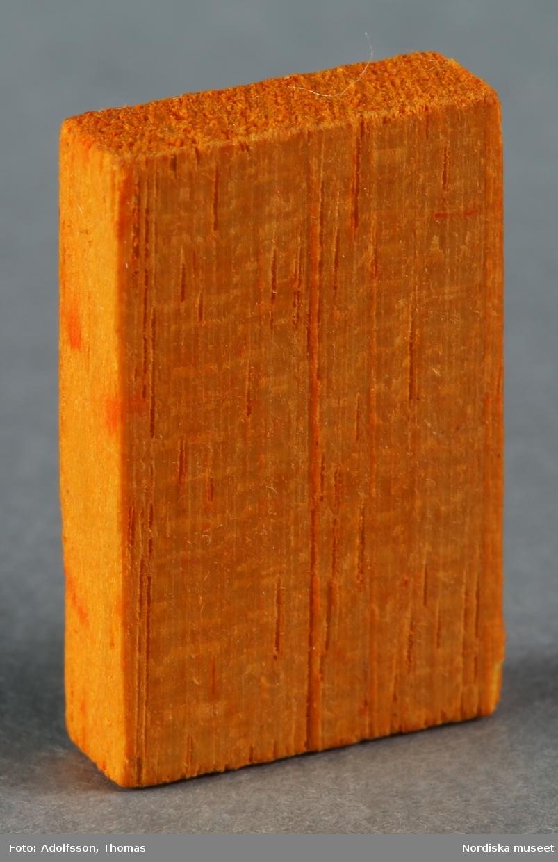Bok av trä, miniatyrstorlek, som är placerad i en liten låda (NM.0333482) med två fack. Hör till flickrummet i dockskåp NM.0331721+.