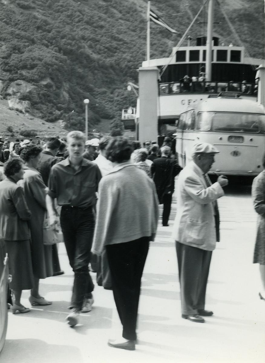 """Motiv av en folkemengde på fergekaia i Geiranger. Ferga """"Geiranger"""" ligger til kai og en rutebuss er på vei ombord."""