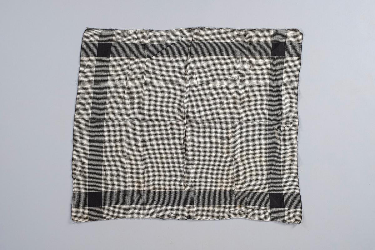 Rektangulært tørkle i svart-hvit bomullstekstil. Sydd for hånd i ene kanten. Motiver: ruter, striper og kvadrater.