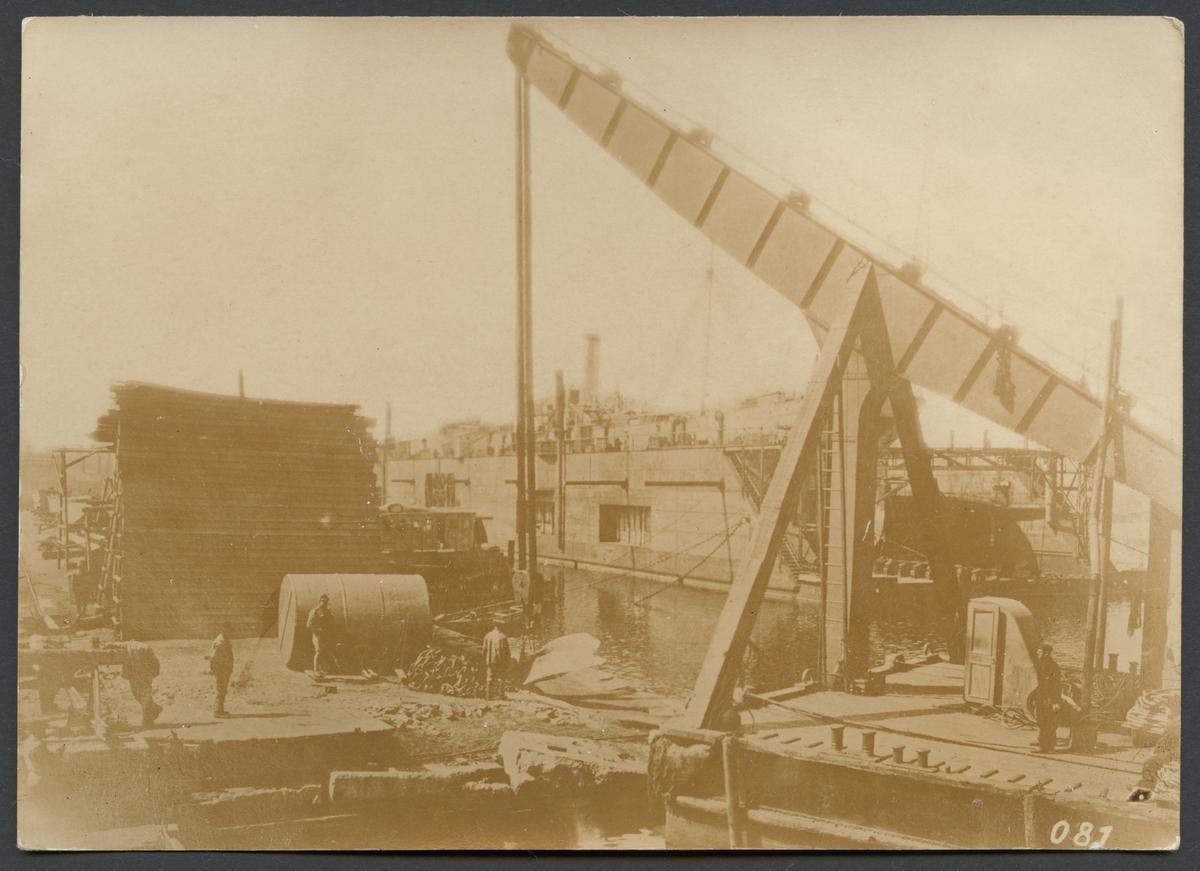 Bilden visar hamnarbetare på en kaj i Odessas hamn. Förgrunden domineras av en lyftkran och i bakgrunden syns en flytdocka.