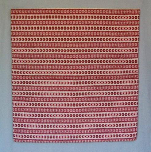 Kuddvar, två stycken, sytt som ett örngott med ficka. I varpen är det blekt bomullsgarn och i inslaget vitt och svart eller rött ullgarn, möbeltygsgarn. Den invikta fickan är vävd i tuskaft utan mönster och endast zick-zackad i kanten.  Det svarta kuddvaret är märkt med R35:1 och det röda med R35:2 på ett vitt bomullsband.  Kuddvar med modellnamn Ros är formgivet av Ann-Mari Nilsson och tillverkat av Länshemslöjden Skaraborg. Det finns med  på sidan 82-83 i vävboken Inredningsvävar av Ann-Mari Nilsson i samarbete med Länshemslöjden Skaraborg från 1987, ICA Bokförlag. Se även inv.nr. 0001-0034,0036-0040.