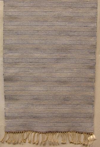 En kraftig och stadig hårgarnsmatta i inslagsrips med tvistränder. I varpen är det linmattvarp. Avslutningen på mattan är 110 mm långa drejade fransar.  Se även inv.nr 0040:2 Vävprov, Prov hårgarnsmatta.  Mattan är märkt med R40:1 på ett vitt bomullsband. En pappersetikett är fastknuten vid fransen. Den maskinskrivna texten lyder. Matta RAN, Formgivning: Ann-Mari Nilsson, Skaraborgs läns hemslöjdsförening, Skövde.  Matta med modellnamn Ran är formgivet av Ann-Mari Nilsson och tillverkat av Länshemslöjden Skaraborg. Det finns med  på sidan 94-95 i vävboken Inredningsvävar av Ann-Mari Nilsson i samarbete med Länshemslöjden Skaraborg från 1987, ICA Bokförlag. Se även inv.nr. 0001-0039.