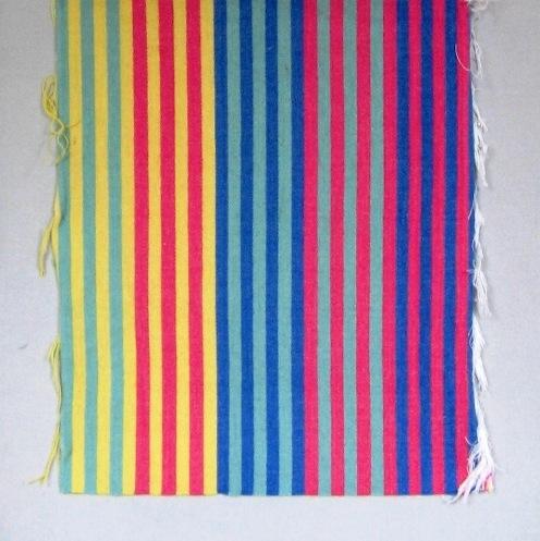 Randigt vävprov, möbeltygsprov, i skarpa nyanser av rosa, gul, blågrön (turkos) och blå. Ett kraftigt möbeltyg vävt i korskypert med inslagseffekt på rätsidan. Varpen är av tunt blekt tvåtrådigt bomullsgarn. Inslaget är entrådigt ullgarn. Ränderna är centimeterbeda och grupperade i bårder med följande kombinationer: turkos/gul, gul/rosa, blå/turkos,  rosa/turkos och rosa/blå. Det är sju ränder i varje bård.  Vävprovet med modellnamn Radar är formgivet av Ann-Mari Nilsson och tillverkat av Länshemslöjden Skaraborg. Vävbeskrivningen har varit publicerad i Tidskriften Hemslöjden nr 4 1987. Se även inv.nr. 0125-0130 Vävprov och Möbelklädsel i olika färgställningar och material.