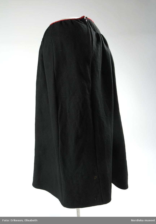 Kjol av svart ylletyg med 10 cm bred rynkning i midjan, i linningen ett handvävt band lagt om rynkningens överkant. Kjolen består av fem våder varav fyra våder är omkring 65 cm breda. Mitt fram en 20-23 cm bred, slät våd, skarvad av två stycken. Intill den smala våden ett 34 cm djupt sprund. I midjan tätt lagda veck i s.k. stripad rynkning, som hålls på plats med fyra rader tvärgående trådar på baksidan, s.k. knäppt rynkning. Längsgående sömmar till synes maskinsydda, för övrigt handsytt. Handvävt band i midjelinningen med mönster av rött yllegarn mot utsidan och ränder av rött och lila yllegarn mot insidan, små stygn antyder att det kan vara två ihopsydda olika band. Midjelinningen hålls ihop med två par hake och hyska, varav en hake saknas och en hyska har släppt från linningen och hänger fast i kvarvarande hake. Kjolens nederkant är fodrad runt om med ett 18 cm brett bruntonat, fläckigt bomullstyg.  Anm: En hake saknas och en hyska har släppt. I det svarta tyget finns flera små hål och enstaka fläckar. Nederkantens fodertyg är mycket smutsigt och fläckigt.  /2019-09-19 Marianne Larsson