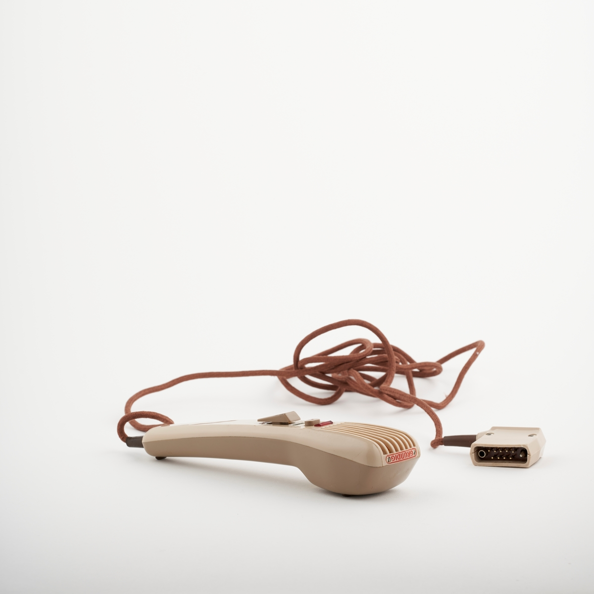 Håndholdt mikrofon. Mikrofonen har to knapper. Den ene er til å starte og stoppe innspilling.  Er sansynelig blitt solgt av frimaet til Gustav Alfred Ring. Firmaet ble etablerte i Kristiania i 1915 og drev import og salg av maskiner til butikker, restauranter og kontorer.  NAV-samlingen er en gruppe av gjenstander som har vært anvendt på sosialkontoret (Aetat - NAV) i Skedsmo kommune.