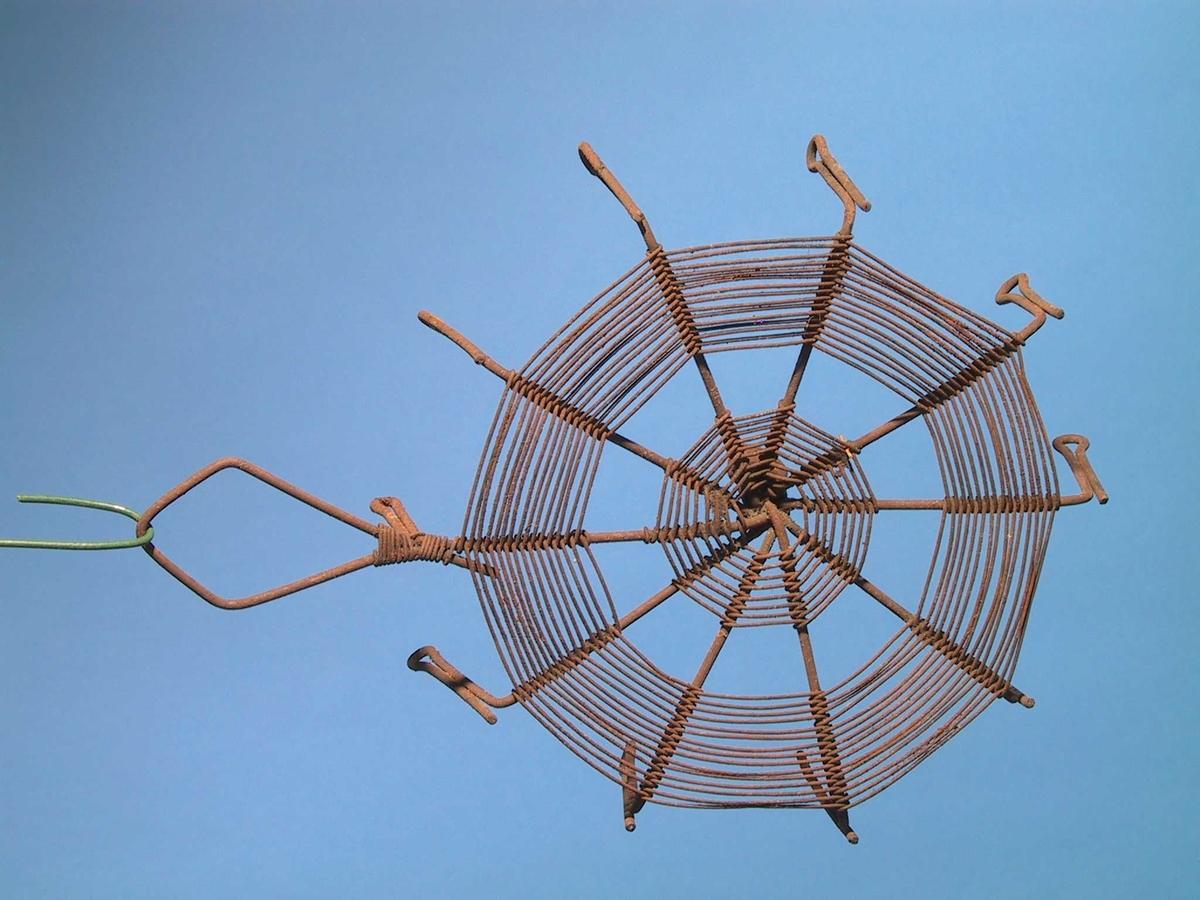 Grytefot, laget av ståltråd, med 11 bein og handtak. To ulike tykkelser tråd, som er bøyd og viklet sammen..