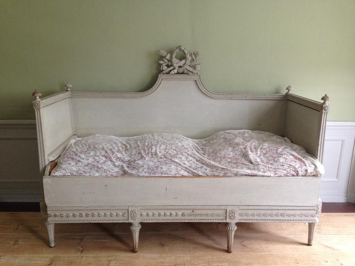 Säng, gustaviansk, vit utdragssäng, med upphöjt mittparti på ryggen, och prytt med krön, skulpterat med fackla, pilkoger, oval krans och lagerkvistar etc. Benen nertill smalnande. Höjd t.o.m. krönfiguren/1.45m  längd 1.90cm  bredd 0.70m.