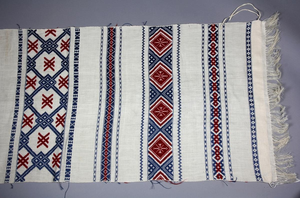 Hängkläde, handvävt, med linvarp och inslag i lin och ull. Botten i tuskaft, plockade bårder i upphämta i rött och blått. Bårder med rutmönster och stjärnor. Kopia av NM.0038635 från Blekinge.
