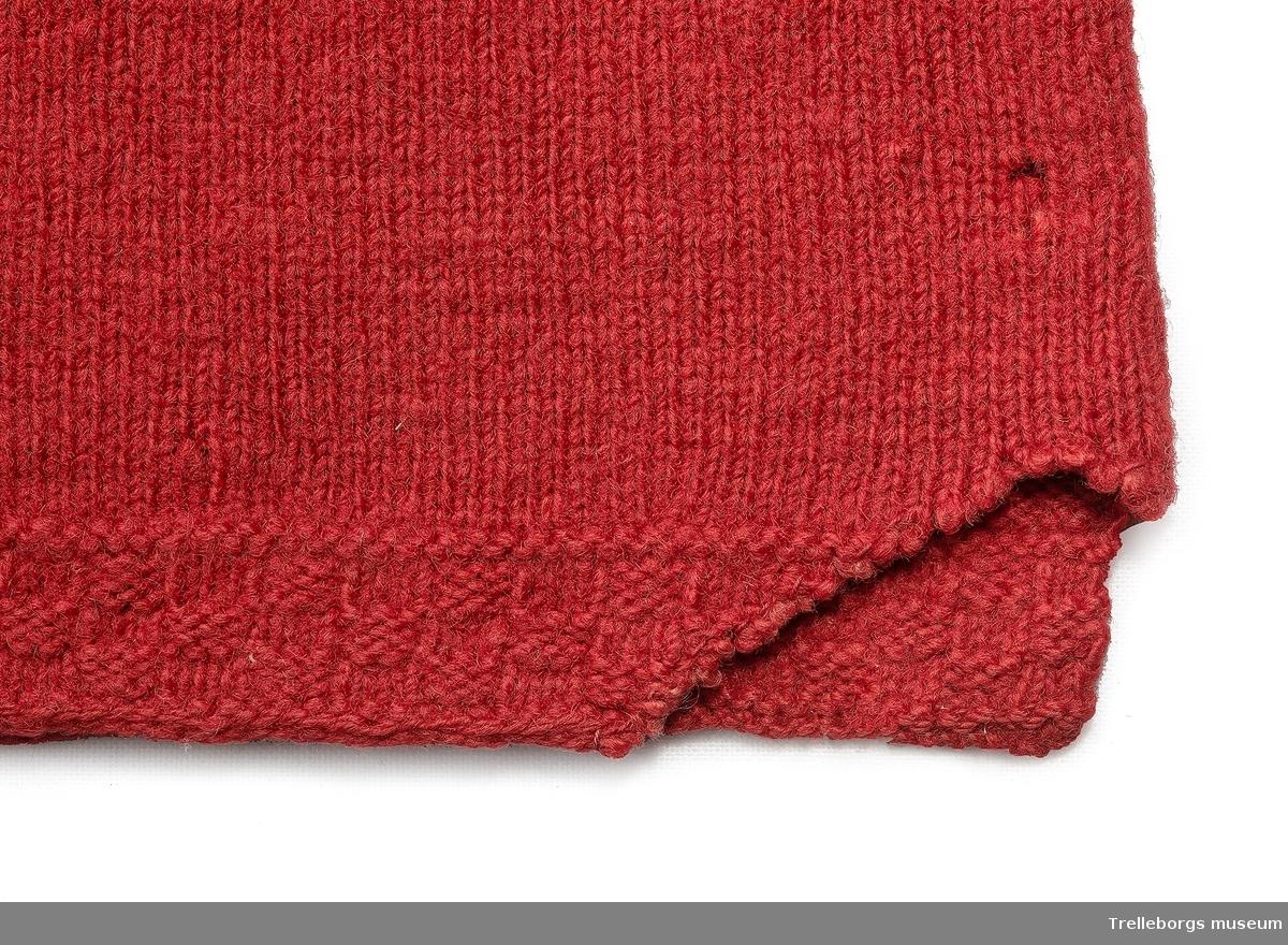 Klarröd mönsterstickad spedetröja med smal bård nertill, slätstickning cirka 9 cm därefter mönsterstickning med stjärnor och fyrkanter. Den runda halsringningen har ett kort sprund i nacken som knäpps med hyska och hake, framtill är urringningen dekorerad med ett 7 cm brett sidenband som kan ha varit rött(?), sidenbandet är broderat med silkestråd 1832 GB samt två blommor. Svart och vit  x-ning runt sidenbandet, även på bandet vid vikningar. Långa ärmar som är mönsterstickade hela vägen, nertill är de avklippta och ett stycke tunnare mönsterstickning är infällt. Skarvarna döljs av ett smalt och ett brett sammetsbrokadband, ytterst avslutas ärmen med en kant av stickade taggar och har uppklippta ärmsprund.