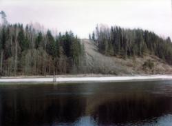 Randselva  i forgrunnen med grustak og skog i bakgrunnen.