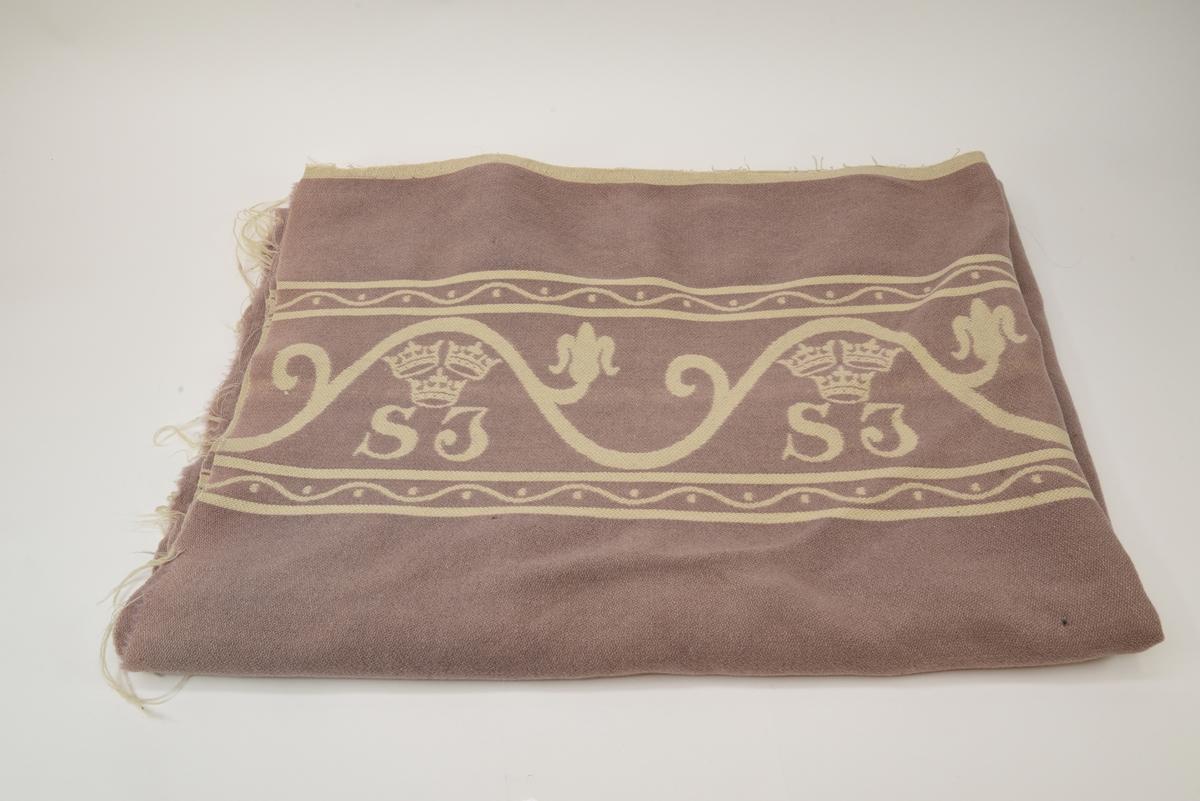 Filt med rosa botten och vit dekor i form av bård med SJ krönt av tre kronor i i vågmönstrad slinga med stiliserad blomma och blad över varje logotyp. Slingan är inramad av två band upptill och nedtill med en vågmönstrad linje med prickar på omväxlande sidor. Vit kant upptill och nedtill.