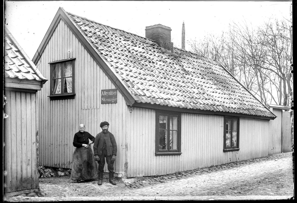 Vogts gate 8, tidligere gatenummer var Vogts gate 7 i Moss, Huset er revet.  Ifølge folketellinga for 1914 var det to leiligheter  i bygningen. Gårdeier var Martin Johansen som var vognmann og bodde med kona i den ene leiligheten. Skomaker Anders Brynildsen var enkemann og bodde i den andre leiligheten, og leide antakelig ut et rom til Helen Engebredtsen f. 1838 i Såner, hun var uten arbeid.  Altså må de to personene på bildet være vognmann Martin og kona Anne Kristine Amalie, ikke skomakermesteren, kona til skomakeren døde i 1912. Martin var metodist og han og kona hadde to barn Sigurd f. 1886, dampskipsstuert som tok hyre i 1909, og datter Arinda f. 1890 som var butikkjomfru i kolonial, ingen av dem bodde altså hjemme i 1914. De hadde fire levende barn utover de som er nevnt, men ingen av dem bodde lenger hjemme på dette tidspunktet (de var født mellom 1873 og 1879). Martin Johansen er ikke oppført i adressekalendre med egen vognmannsforretning, så han arbeidet antakelig som vognmann for en av de vognmannforretningens i Moss. Tidligere hadde han arbeidet som fyrbøter på Moss glassverk (1900). Vogts gate 7 ifølge Adressebok for Fredrikshald, Fredrikstad, Moss, Sarpsborg 1911-12.  Skilt: A. Brynildsen Skomager.  A. Brynildsen var f. 27.09.1833 i Hobøl d. 9.1.1919, skomakermester og kona Anna Helen Brynildsen f. 1837 i Vestby, d. 15.8.1912. Folketelling 1914 bodde Anders og Helen i Vogts gate 7.  Anna Helen døde 15. august 1912. Arve Tomt Gundersensier at dette seinere blei til Vogts gate 8.