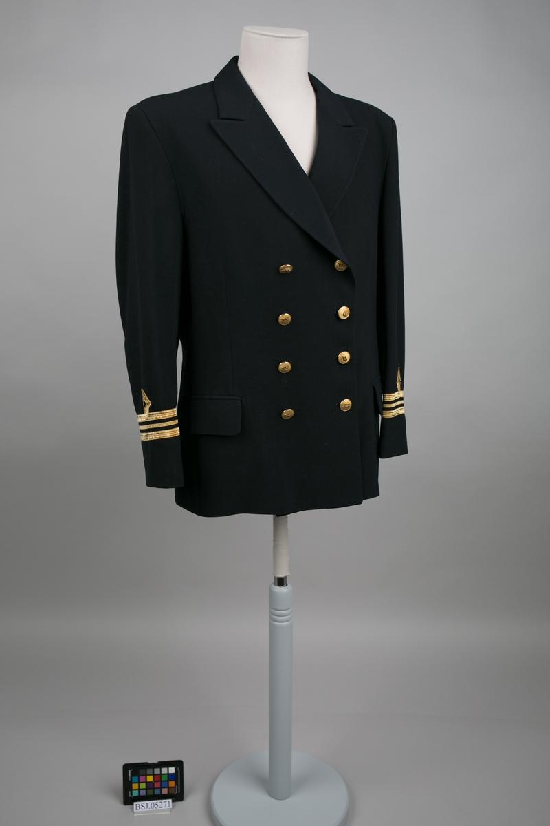 Overstyrmann uniformjakke med 3 stk. gullbånd og påsydde distinksjoner på erme. Dobbelspent med til sammen 8 stk. knapper i gullfarge med emblem fra rederiet Royal Viking Line.