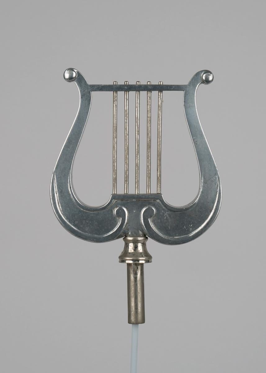 Faneutstyr fra Bergens Losse- og Lasteforeningen. Toppspyd formet som strenginstrument lyre, i metall. Med tapp til feste på fanestang.