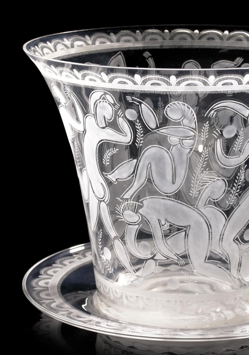"""Design: Edward Hald. Stor skål på fat """"Bollspelande flickor"""", med graverat motiv av just bollspelande flickor. Bilden har stark koppling till den stil som framför allt kopplas till Matisse, som Hald gick i lära hos under tiden han studerade konst i Paris."""