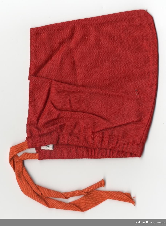 KLM 28082:304 Dockhuvudbonad, dockhätta, av bomull och konstmaterial, röd. Nertill kantad med kanalsöm, däri bomullsband, rött, som dras ihop runt hals och knytes framtill. Huva, bak, upptill med topp.