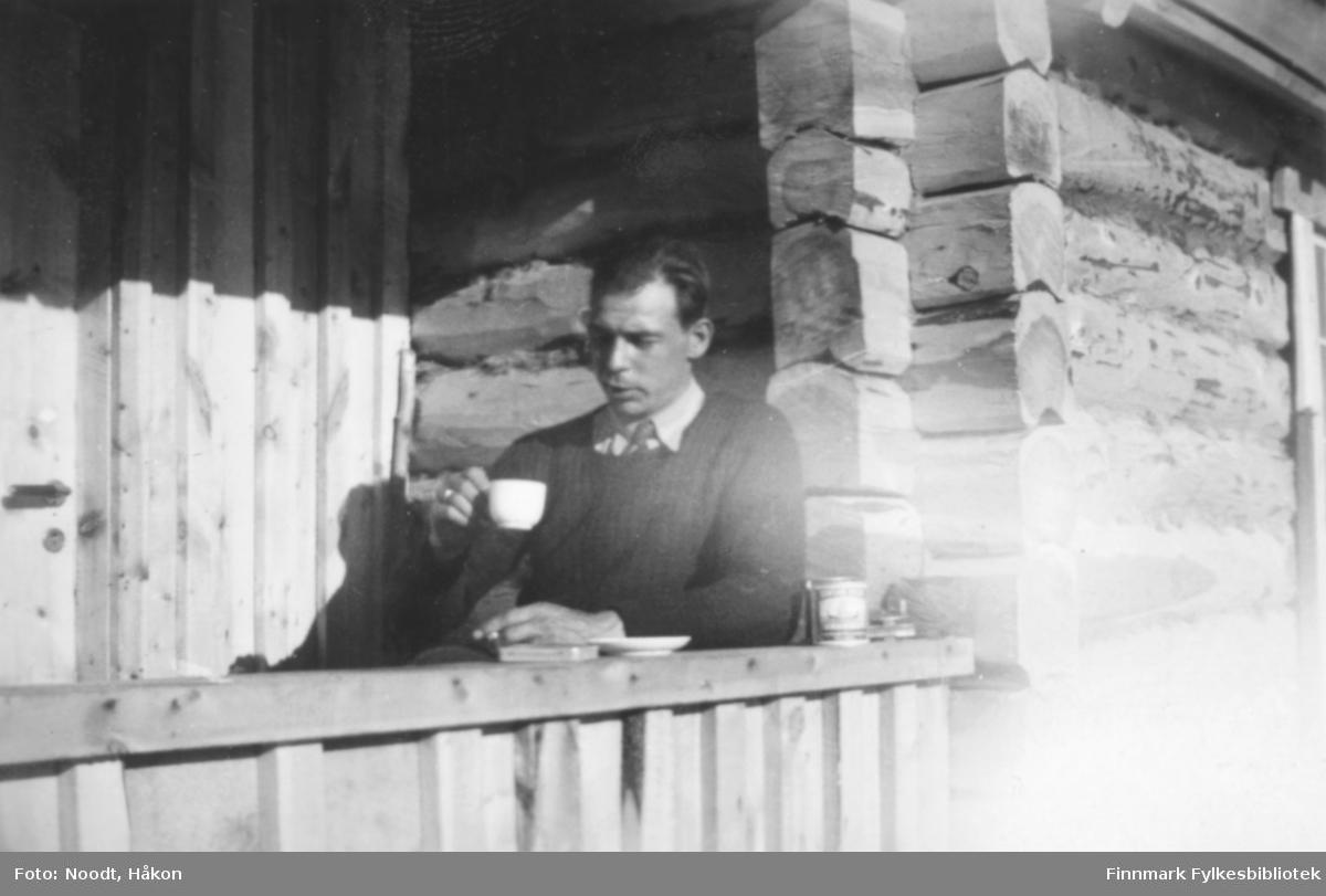 Leif Noodt drikker kaffe på verandaen på skogvesenets hytte ved Stellingvann i Porsanger, 1938.
