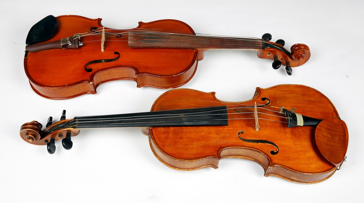 """2 stk m/buer og kasser, og tilbehør (kolofonium og trekk)  Chr.Deåphin,Lillehammer.No 87.Modell Strad.Stol mrk.Aubert A Mirecourt.L 60 B 21 H 3.5 b:Fiolin,innv.mrk.Parrot Violin nr. 1410.Tientsin,China. L 59 B 21 H 3.5. c,d:Fiolinbuer,c m/koppertrådsurring.L74B2.5 e:Reserve-stol. f:filt-teppe(til å dekke fiolin med) L 65 B 22. g:Fiolinkasse,sort,foret m/grønn filt,4 rom.L 80 B 32 H 12. h:Brunt lerrets-overtrekk for kassen,glidelås langs kanten.L 80 B 33 H 12. i, j: Esker med kolofonium til buene.""""""""       """""""