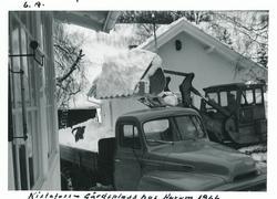 Traktor brøyter snø som plasseres på lastebil på gårdsplasse