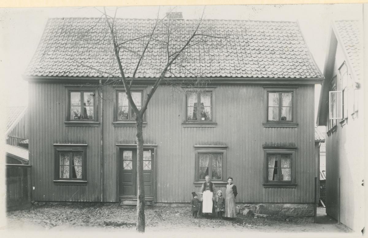"""Klostergt., fire bilder, ca. 1910. Trykk på pilen.  Bilde 1: Nr. 5, bygget før 1800.  Bilde 2: Nr. 7, bygget ca. 1815.  Bilde 3: Nr. 9, bygget i 1816.  Bilde 4: Nr. 11 - """"Blondingården"""". En av de eldste gårdene i strøket, bygget før 1837. Posering utenfor."""