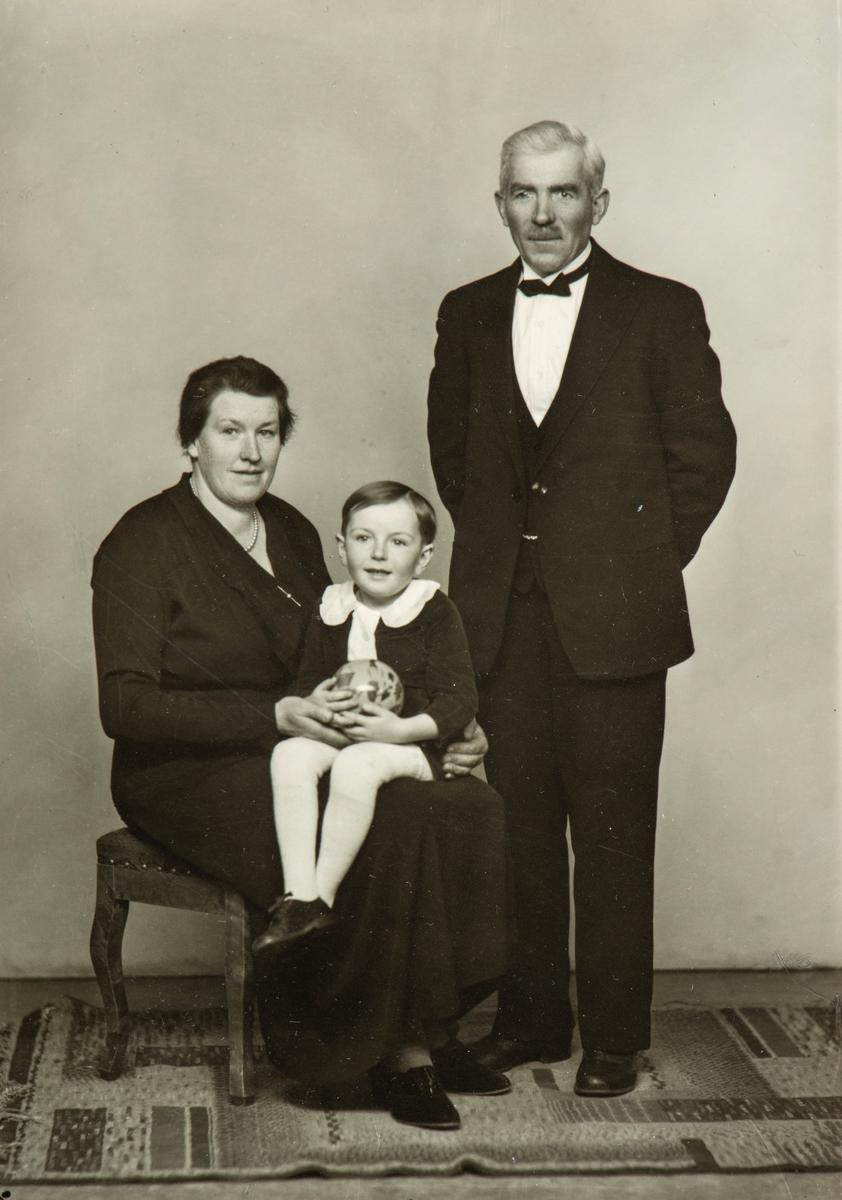Familie gruppe 3.  Anna Kinn-Berntsen med sønnen Ole Martin Kinn-Berntsen på fanget, Olaf Berntsen stående ved siden.  Olaf var gårdsarbeider på Staur gård. Anna jobbet som bygdekokke.