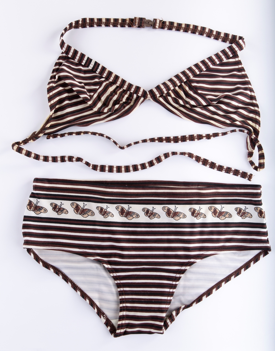 Bikini A: Brystholder. Uten innlegg. Nakkestropper knyttes sammen. Plastlukking bak. B: Truse Tverstripet. Over magen en bord av sommerfugler. Sprø strikk i linninger på BH og truse.  Bruker: Anne Stine Barli