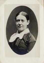 Porträttfoto av en kvinna i mörk klänning med vit, spetskant