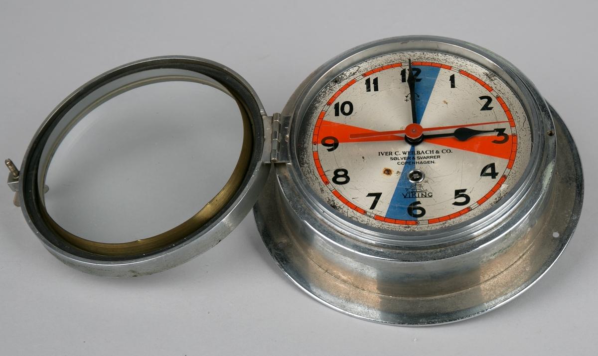 Veggur til skip. Radiour formet som koøye med glasslokk over visere og urskive som åpnes ved hjelp av vingeskrue. Trekkes opp med nøkkel (nøkkel mangler).