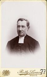 Foto av en man i prästrock och prästkrage m.m. Bröstbild, ha
