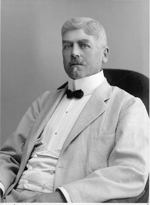 Porträtt av stadsläkare Viktor Lindholmer sittande i en fåtölj. Han bär en smårutik kostym, sidenväst och fluga.