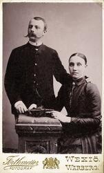 Foto (grupporträtt) av en man och en kvinna. Han är klädd i