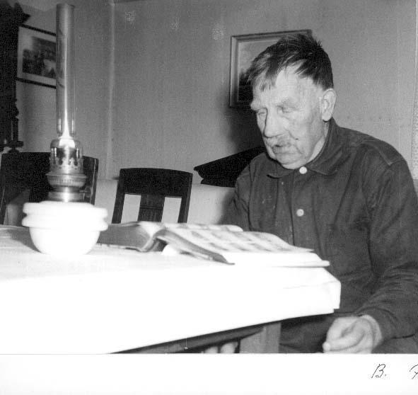 En gammal man, Karl Alfred Johansson Rehn i Sonaby, sitter vid ett bord med en tänd fotogenlampa och uppslagen bok framför sig.