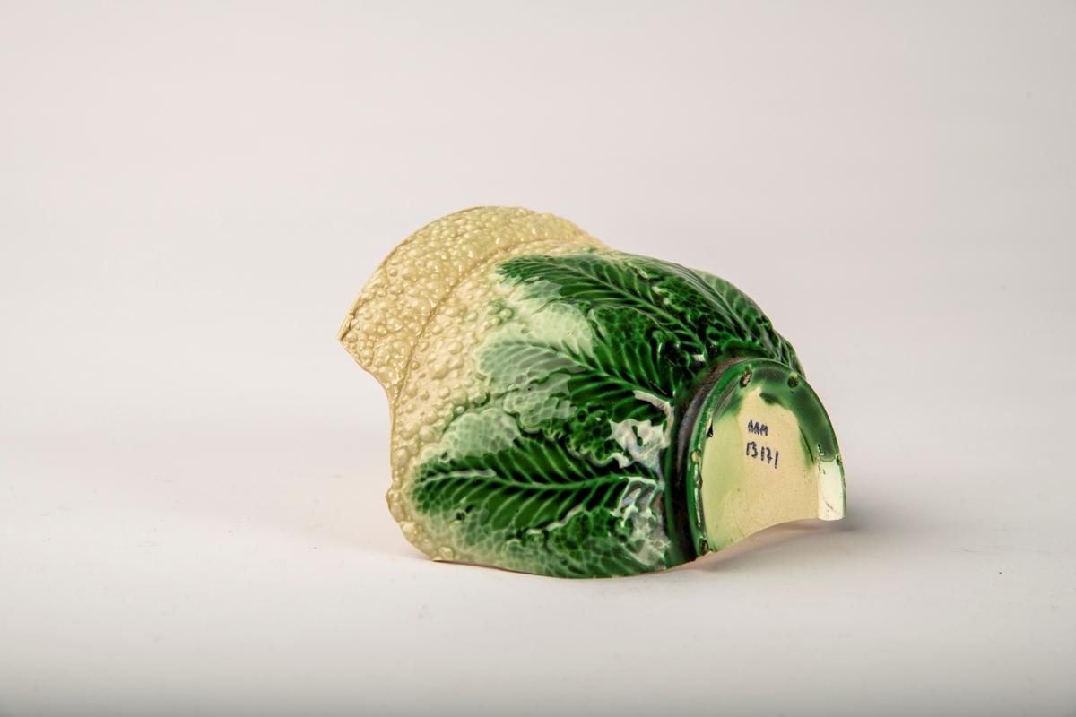 En halv bolle, blomkålmønster.  Wedgewood eller Wedgewoodimitasjon.  Engelsk.  Mønstertypen 1700-talls, men laget også i siste halvdel av 1800-tallet og begynnelsen av 1900-tallet.  Creamware, utvendig grønnglasert relieff med blad nederst, og kremfarget innvendig.  Blomkåltekstur øverst.