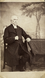 Foto av en äldre man med polisonger, klädd i prästrock och p