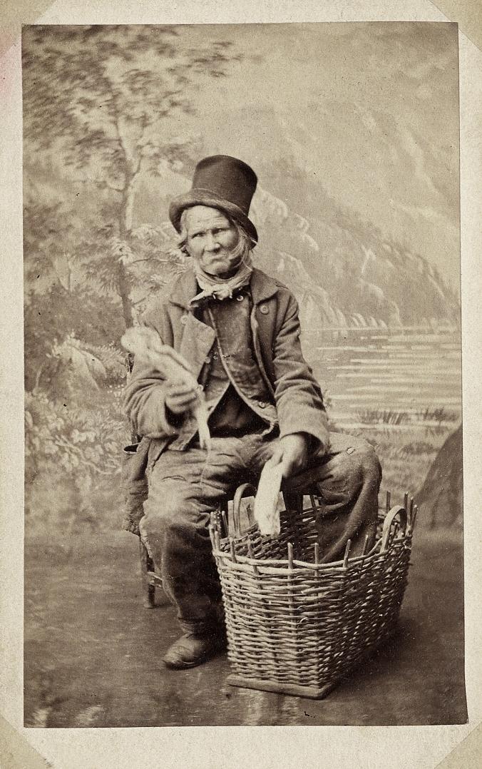 Foto av en man i slitna kläder och en dito hög hatt. Han visar fram några fiskar ur en flätad korg. Helfigur. Ateljéfoto.