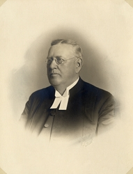 Foto av en man med glasögon, klädd i prästrock och prästkrag