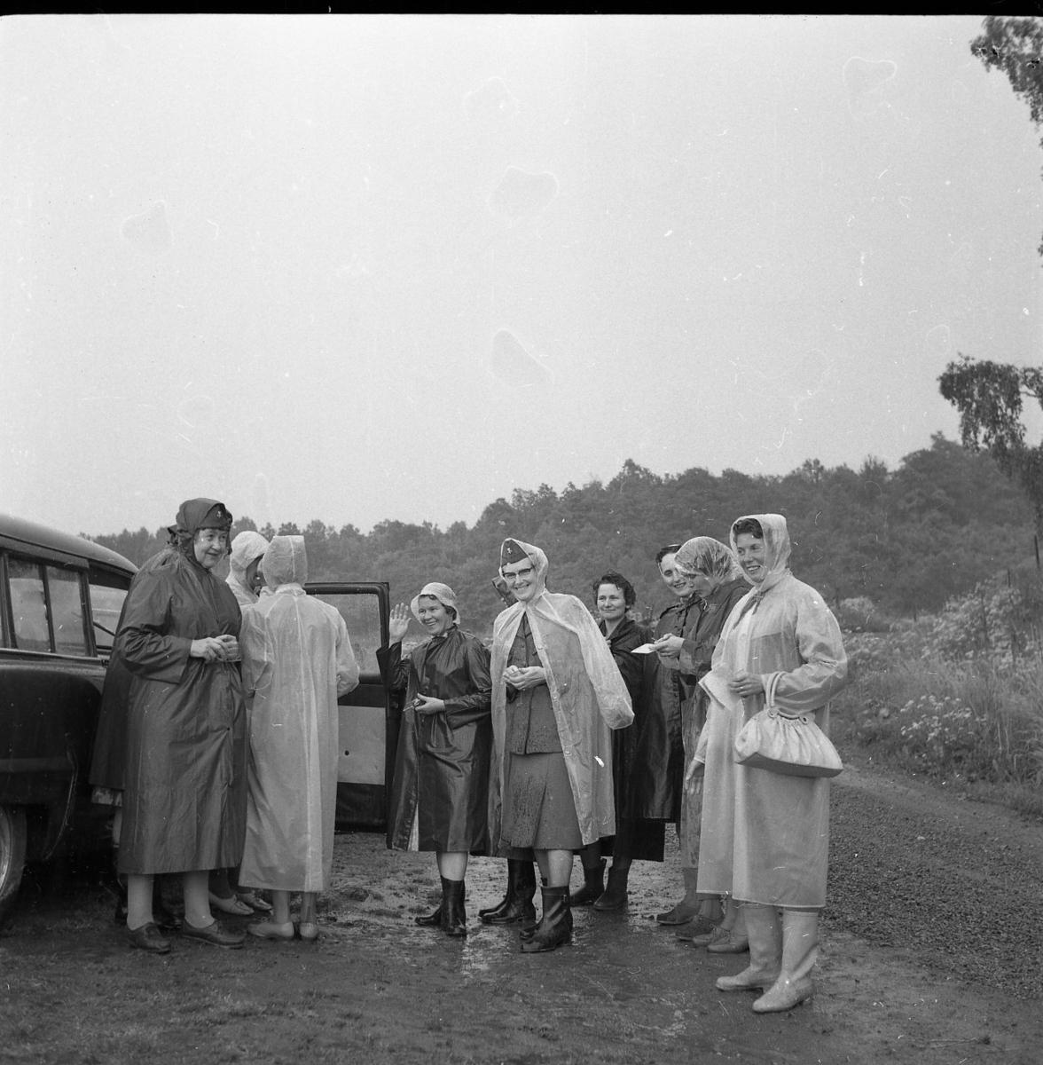 En grupp kvinnor i regnkläder står vid en bil med höger dörr öppen. Det regnar.