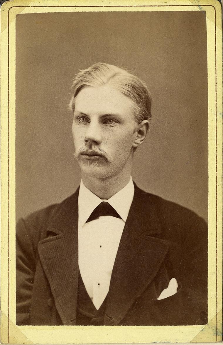 Porträttfoto av en ung man i kavajkostym med väst, stärkkrage och fluga.  Bröstbild, halvprofil. Ateljéfoto.