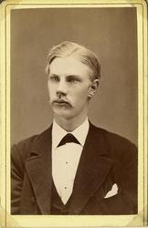 Porträttfoto av en ung man i kavajkostym med väst, stärkkrag