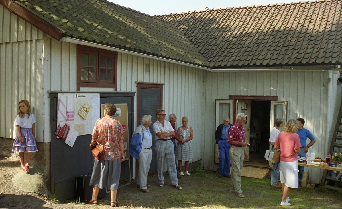 Invigning av Ekebackens Hantverksgård (tidigare John Lindströms möbelsnickeri) på Gamla Riksvägen 81, början av 1990-talet. Besökare står samlade utanför entrén.