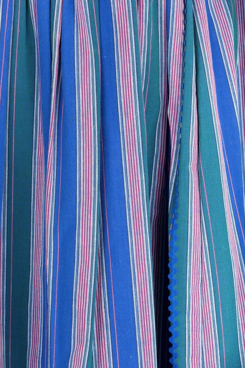 Skjørt i stripet bomullstoff, 7 lett skrådde bredder rynket til linning. Svakt spisset bærestykke forran under linning. Pyntet med kroklisser og bånd Tyrolerstil. Pyntebånd i spiss langs folder og nederst på skjørtet.  Giver ble i 1987 ansatt som adm.konsulent på Follo Museum 1987. Innkjøpt  bl. a. til bruk som arbeidsantrekk på Follo Museum. Brukt sammen med hvit bluse fhm-?