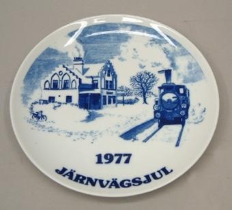 """Vit porslinstallrik med blått tryck som visar en station med rykande ånglok framför. """"Järnvägsjul  1977""""  Denna tallrik har ederats i 200 numrerade ex, av vilka detta är 150. Elgporslin. Design Bertina Kärager."""
