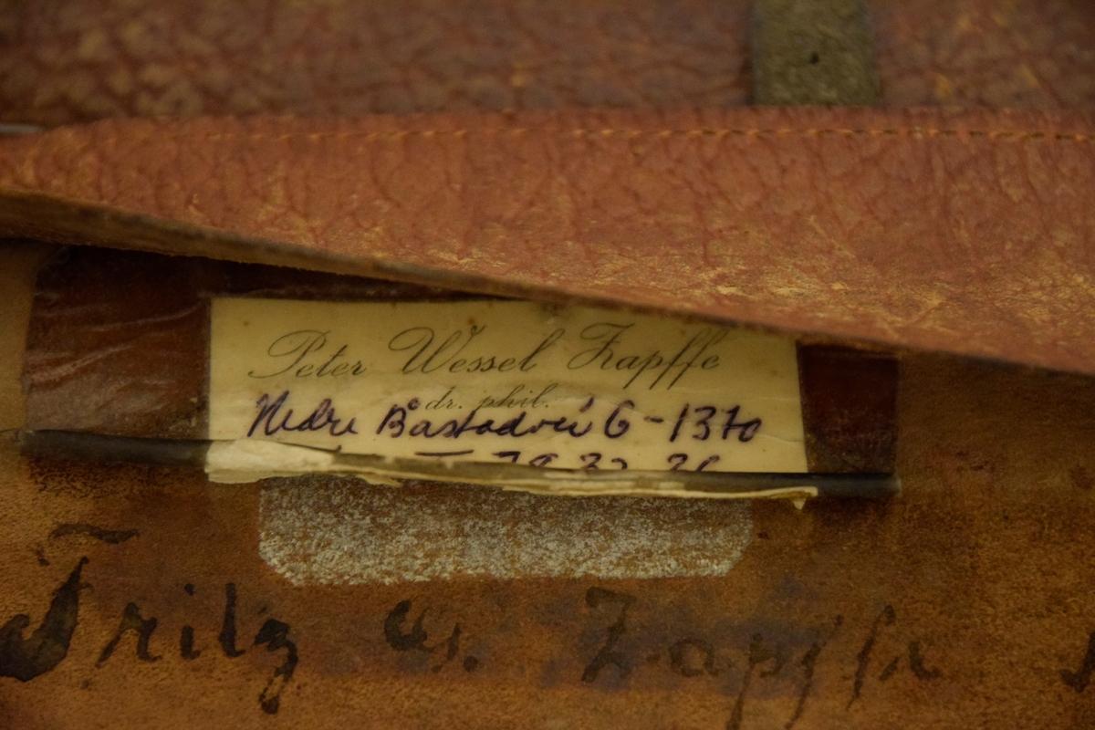 Filosofen Peter Wessel Zapffe og hans kone Berit testamenterte sin eiendom på Båstad i Asker til Universitetet i Oslo. Da det ble besluttet å selge eiendommen i 2009 ble deler av P.W. Zapffes arbeidsrom og andre eiendeler overlatt til Asker Museum. Denne samlingen inngår nå som en permanent utstilling på museet. Veske, dokumentmappe med innhold. Håndtak erstattet med lærrem med spenne og tekstilbånd. Innhold: lommetørkle, diverse penner, panodil, refleks.