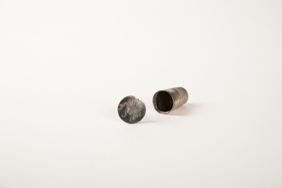 Sidelukket futteral som består av to like deler med profil som et fingerbøl. Foret med hvit silke. I den ene halvdel en fingerbøl av sølv. Inni den en fasettert glassflakong med rester av brunt innhold. Sølvbunn, hvorpå inngravert:  K L 1846.