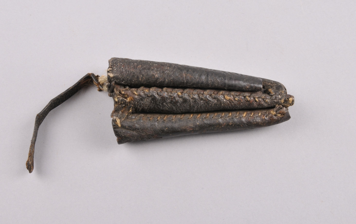 Lærslir med plass til fire knivar. Slira er sett saman av 4 uahengige slirer som er sydd fasst til kvarandre. Dei ahar litt ulik form og storleik.  Oppheng for belte i lær, reparert med hyssing .