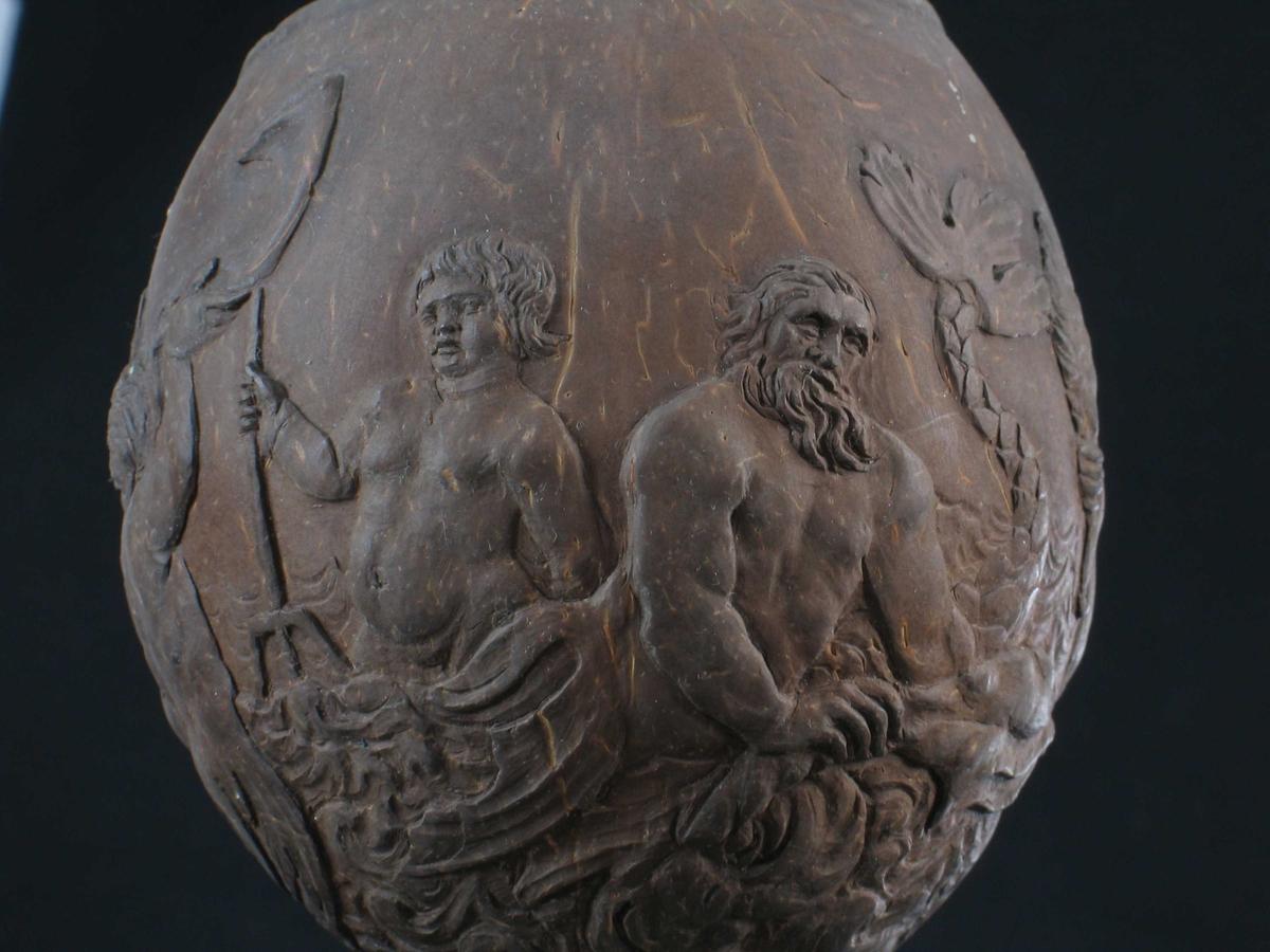 Foten har fire ornamentfelt i relieff, to av dem med blomsterdekor, de to andre med blad og overflødighetshorn. Pokalen bæres av en Neptunfigur utskåret i elfenben, med løftet venstrearm (denne har hatt scepter) og delfin mellom benene. På Neptuns hode en pokal av en kokosnøtt med toppen avskåret som lokk, og med beninnfatning.  Pokalen har relieffutsmykning med nereider og tritoner, som blåser i en koncha (basunlignende instrument). Lokket har fire relieffmotiver med nøtter og to med blomster.  Lokkgrep av ben, balusterformet, med sittende apekatt i metall på toppen.