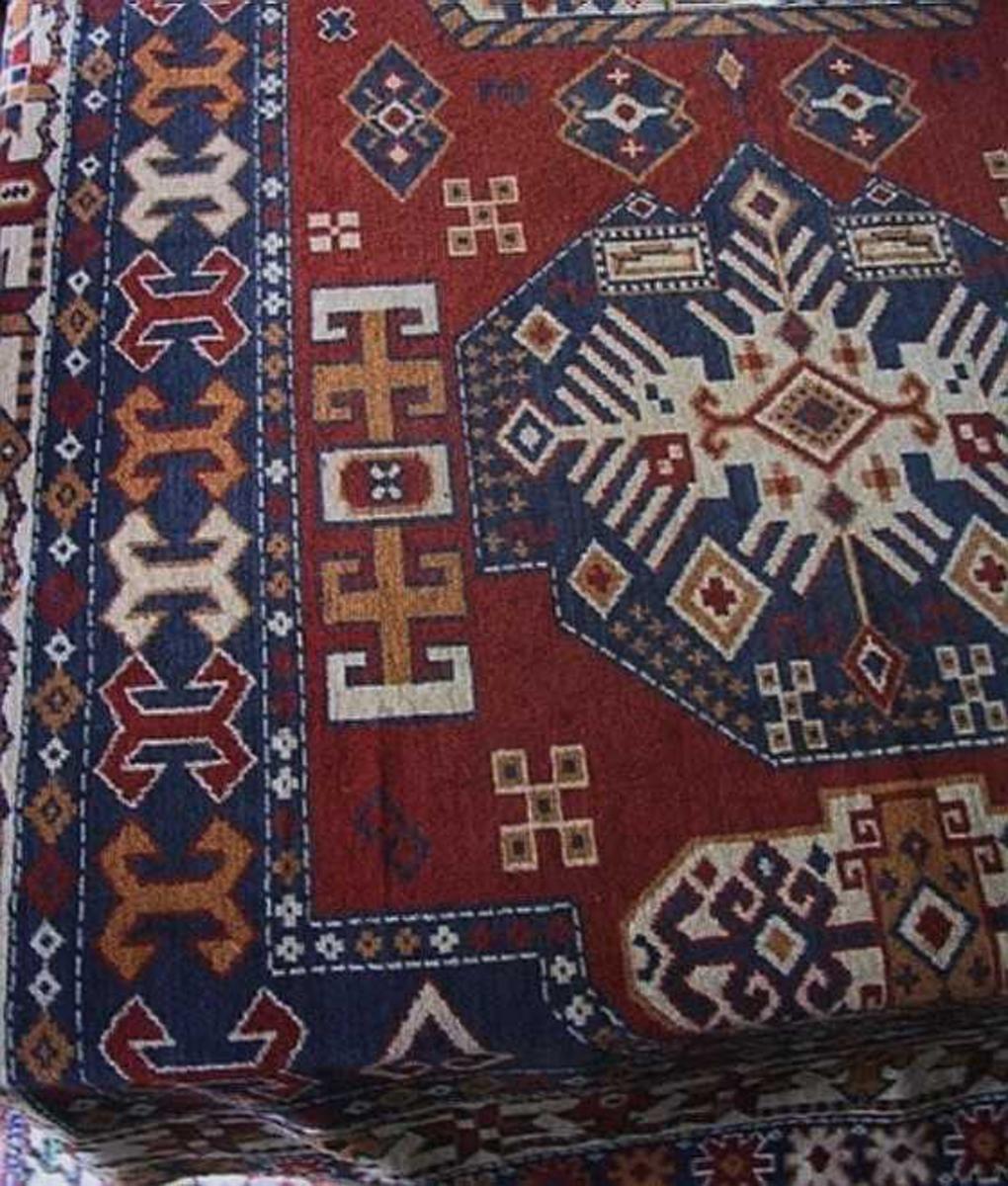 Plysjteppe av bomull, maskinvevet, orientalsk mønster i farvene rødt, blått, gult og hvitt. Sannsynligvis  brukt som divanteppe, muligens bordteppe.
