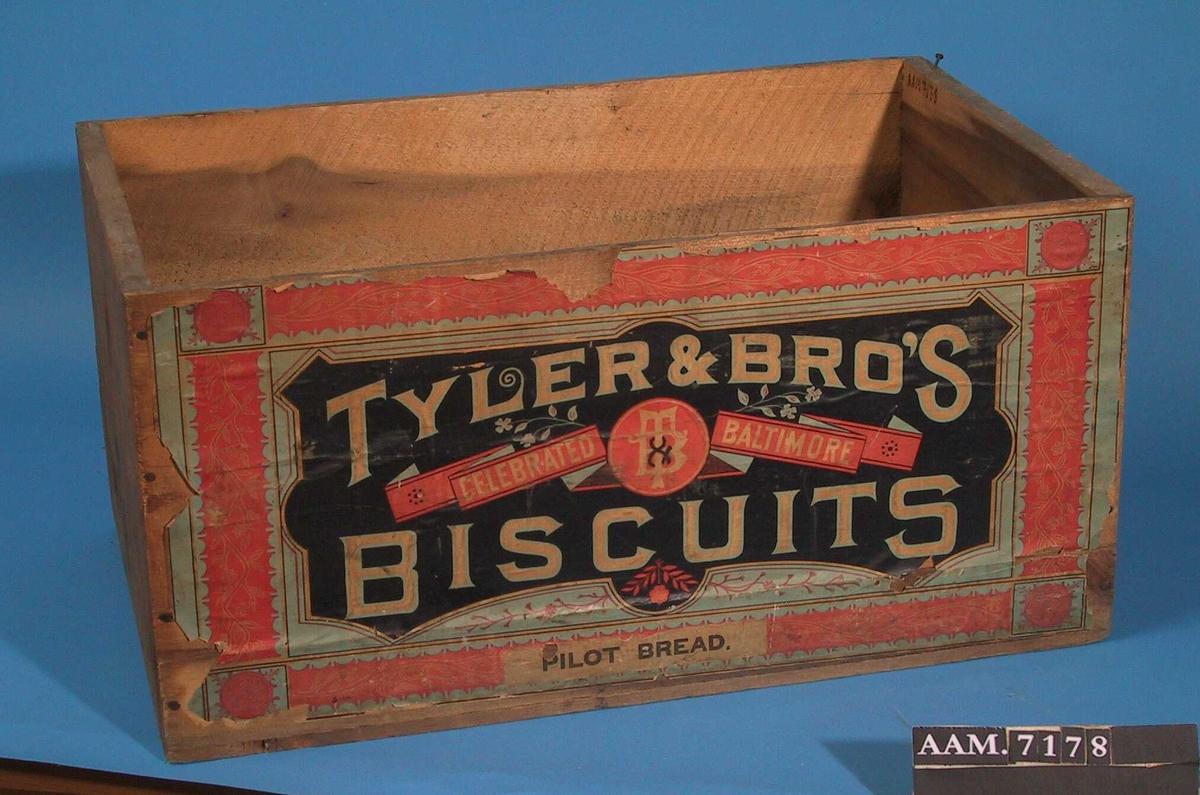 """Kasse. Sort etikett med hvit og lysblå tekst,   rankebord  på rød bunn med lyseblå kanter. Tekst:""""   Tyler & Bros   Celebrated Baltimore Biseuits. Pilot Bread.""""  På siden i sort påtrykt:   Savannah GA."""