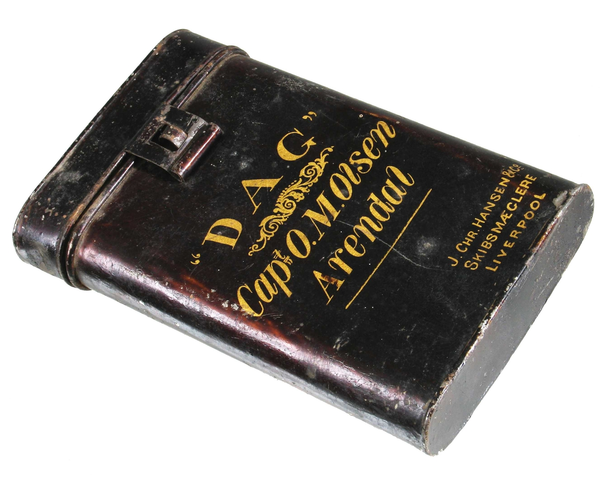 """Dokumentboks  for """"Dag"""", kaptein O. M. Olsen,  Arendal Blikk, malt  kobberbrun,   forgylte bokstaver.  Flat  boks med rundede sider, tekst på forsiden, skip og kaptein nevnes.  Tilst. god."""